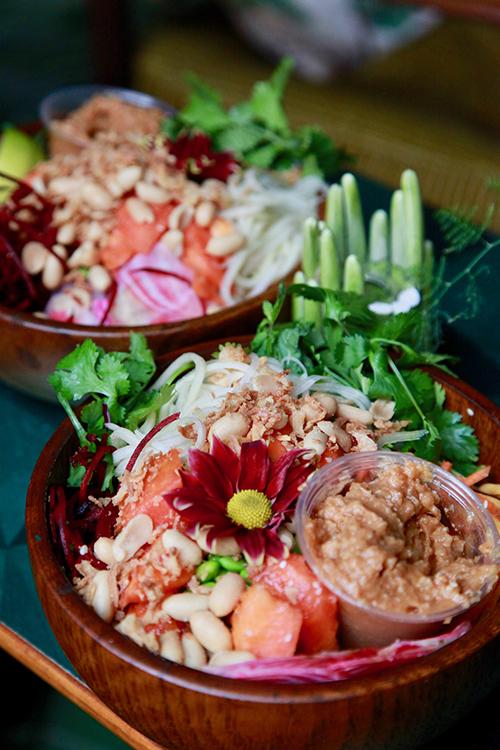 En skål i teak med sallad, en blomma och en röra