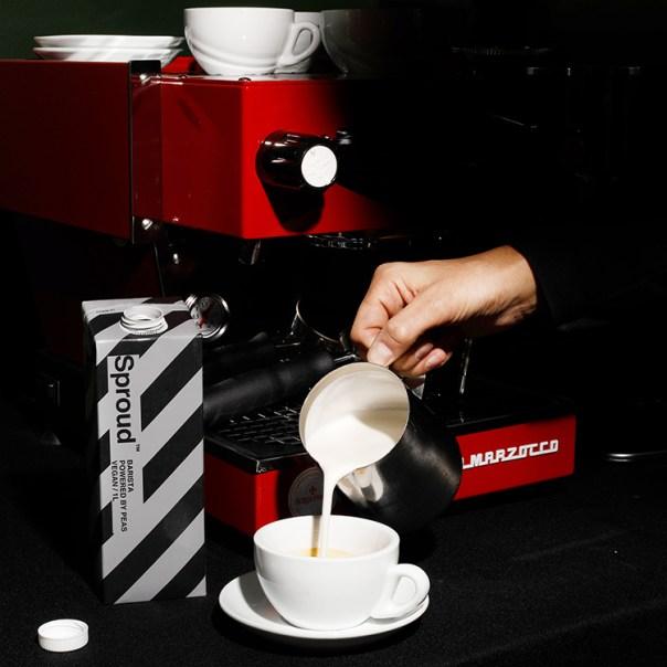 Mjölk hälls i en kaffekopp, till vänster en randig tetra med texten Sproud
