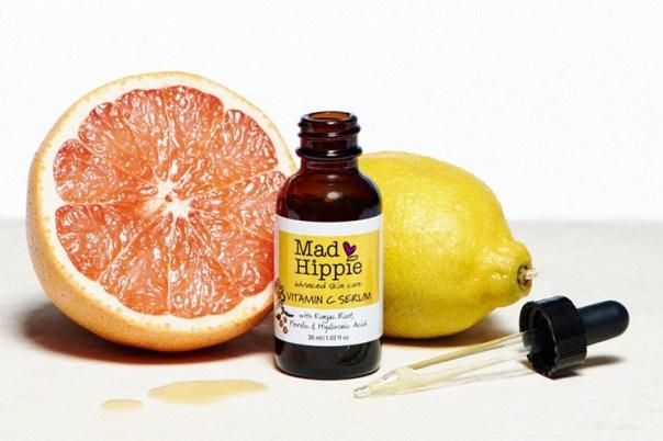 En liten brun flaska med texten Mad Hippie, en delad apelsin och en citron i bakgrunden