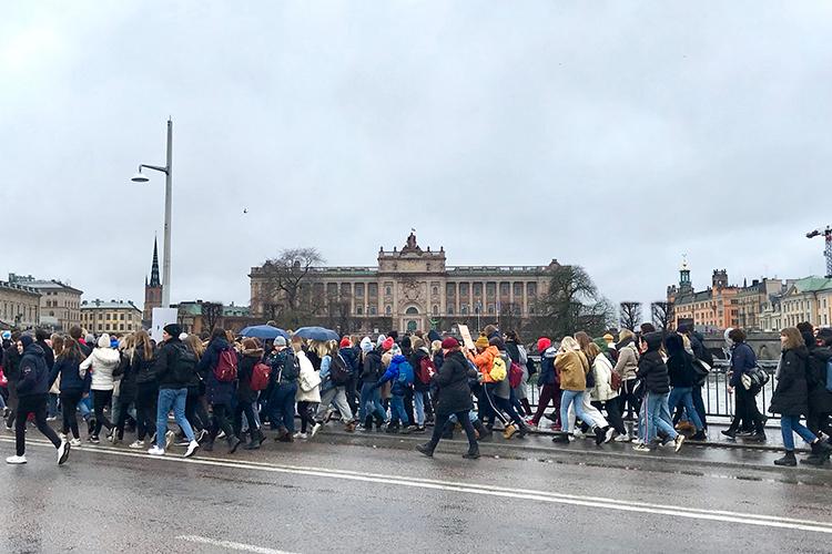 En parad av människor går i regn längs en gata