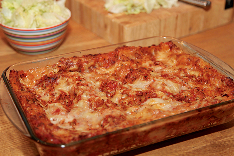 En ugnsform med lasagne, isbergssallad i skål i bakgrunden