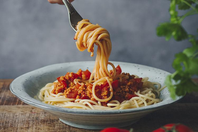 En tallrik med spaghetti bolognese. En gaffel med upprullad spaghetti