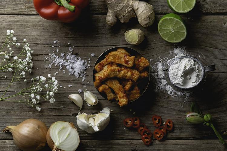 Lök, vitlök, ingefära på ett bord, i mitten en skål med kycklingliknande bitar, Veg Chili Giingerstrips