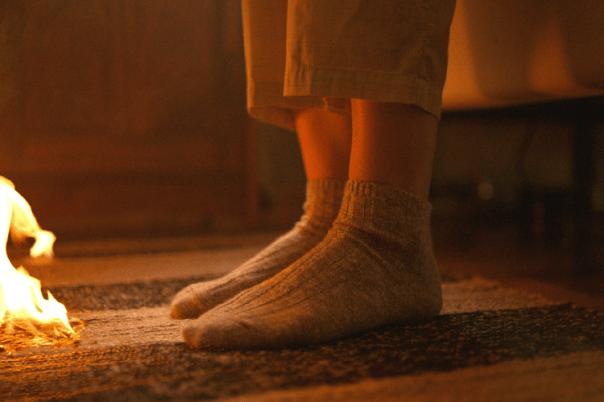 Ett par fötter på en matta och det brinner framför dem