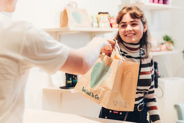 En leende kvinna tar emot en pappkasse med loggan för Too Good To Go