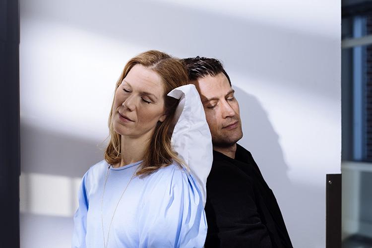 En kvinna och en man lutar sina huvuden mot varandra med en kudde mellan
