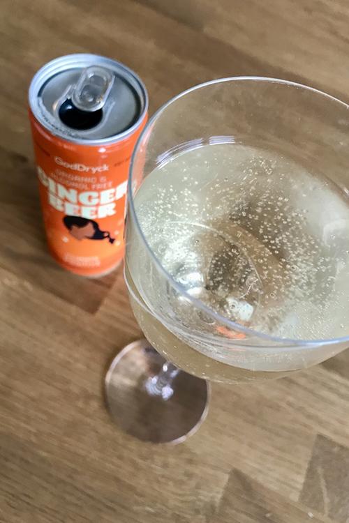 Ett glas med ljus bubblig dryck, bredvid en orange burk med texten Ginger Beer