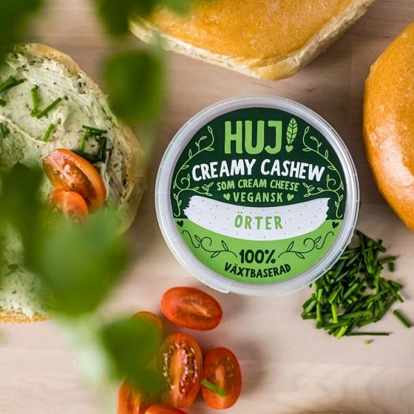 Förpackning med HUJ! Creamy Cashew, smörgås och tomater bredvid