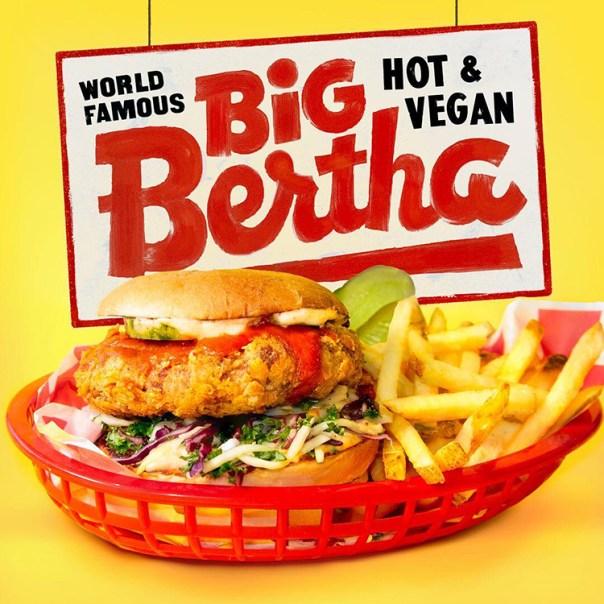 Hamburgare med pommes i röd korg, texten Big Bertha Hot & Vegan ovanför