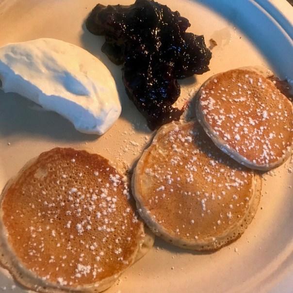 American pancakes med sylt och vispgrädde på en tallrik