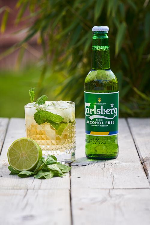 En flaska Carlsberg Alcohol Free med ett glas med is och mynta bredvid