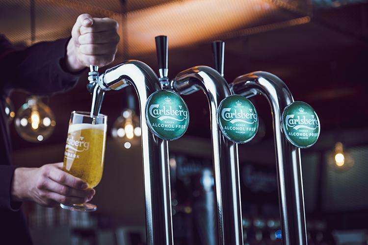 Ett glas öl fylls från en öltapp med Carlsberg Alcohol Free