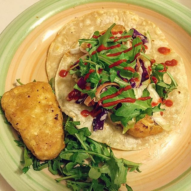 Gardein's Fishless Filets on top of toasted soft corn tortillas with arugula, cabbage coleslaw, and sriracha 😛🌯