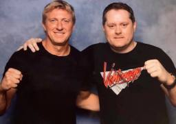 William Zabka (left) poses with fan Ben Clarke, who is wearing a newer variant Vehlinggo logo tee.