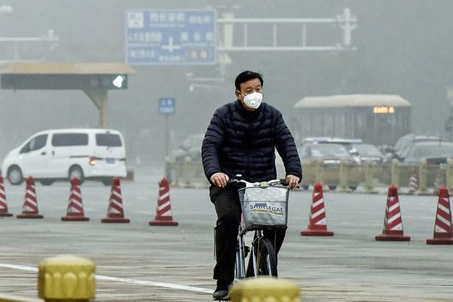 ATAQUE AOS PULMÕES - Ciclista em Pequim: morador pedala de máscara para se proteger da poluição -