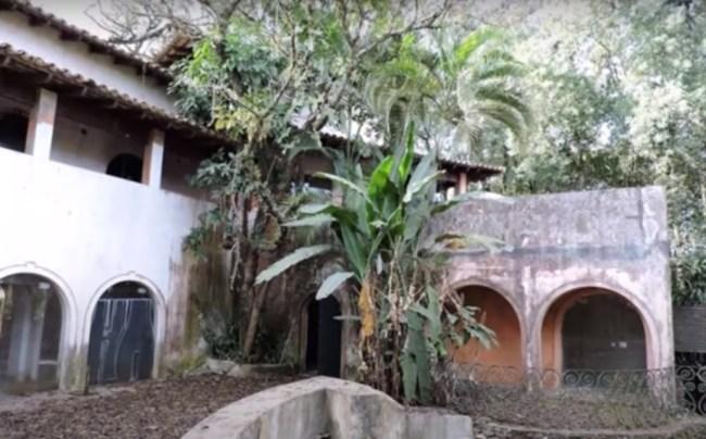 Casa abandonada em meio a árvores e plantas sem cuidados