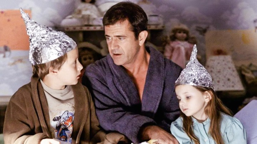 The image shows the pastor, in his robe, holding the hand of two children, saying something to the two who are paying attention.