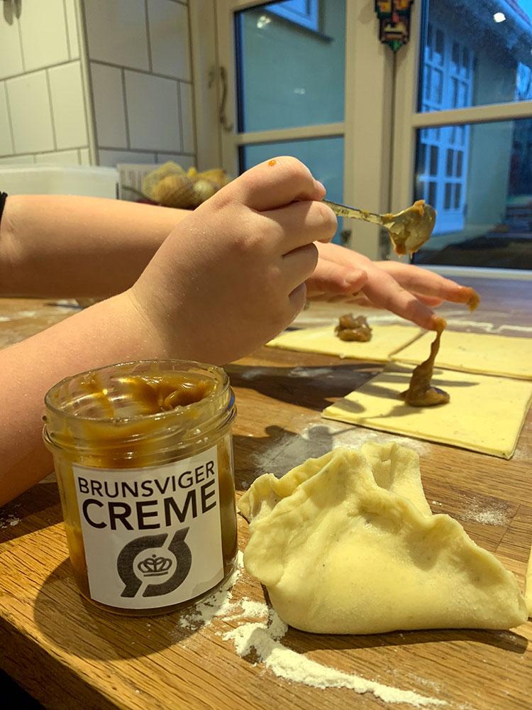 Tilsæt brunsvigercreme og fold hjørnerne på fastelavnsbollerne