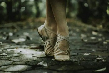 A ballet dancer's feet in pointe shoes on a cobbled street