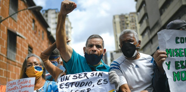 """Protesting teachers on World Teachers' Day (October 5) holding placards that read: """"'An uneducated person is an incomplete person,' Bolivar"""" and """"Low salaries ... enough of misery"""""""