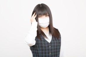 花粉症と風邪で頭痛に苦しめられる女性