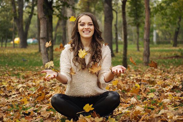 落ち葉の上に座る女性