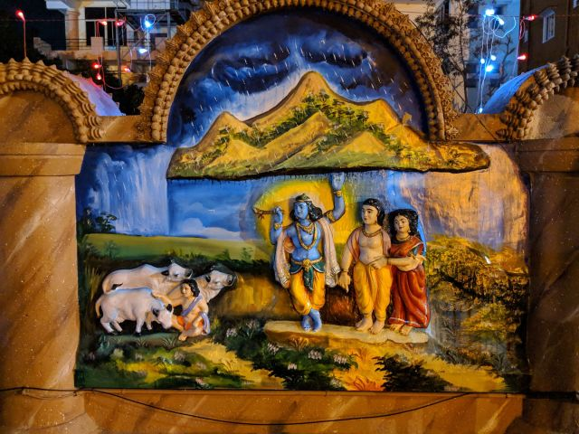 Lord Krishna lifting the Govardhan Giri (hill) to provide shelter to the villagers and their cattle