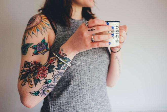 Lady with tattoos holding a mug of coffee