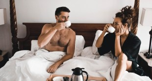 Happy couple sat in bed drinking coffee