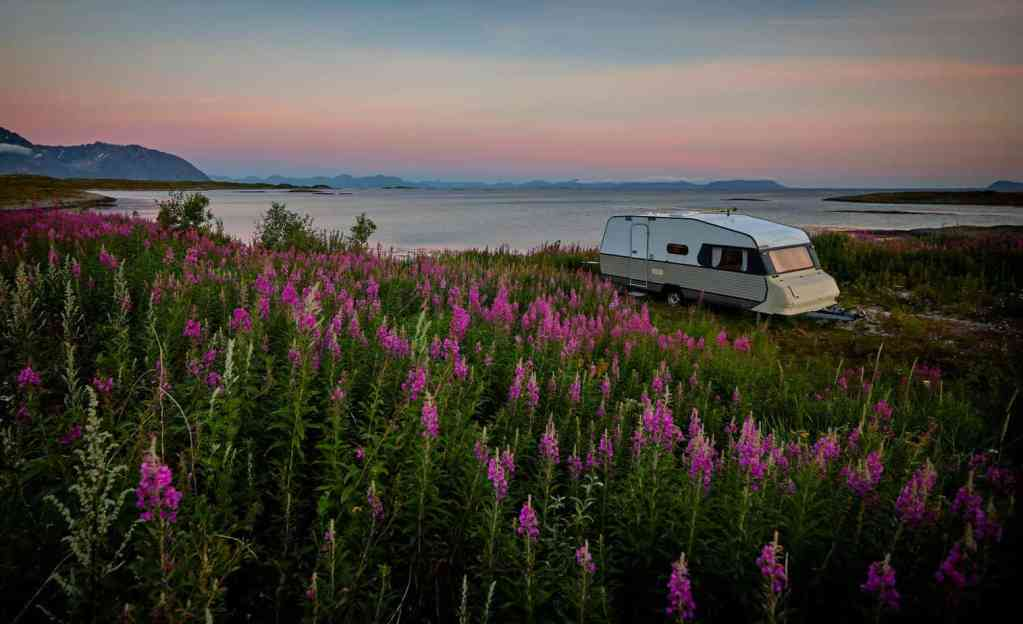 A white RV parked during sunrise in front of a lake with mountains in the background.