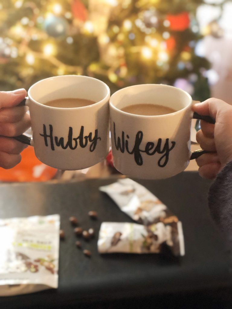Hubby and Wifey coffee cups in front of a Christmas tree with chocolates.