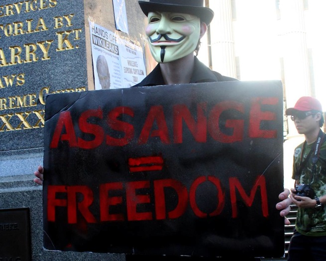 """Anonymous protester holds up """"Assange = Freedom"""" sign"""
