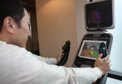Kai Huang plays exercise game on a stationary bike.