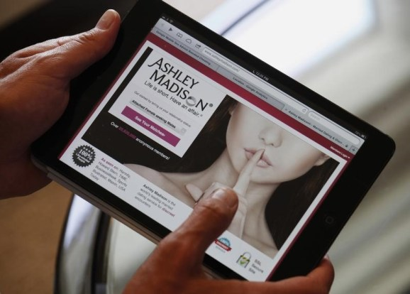Ashley Madison founder Noel Biderman demonstrates his website on a tablet computer during an interview in Hong Kong August 28, 2013.