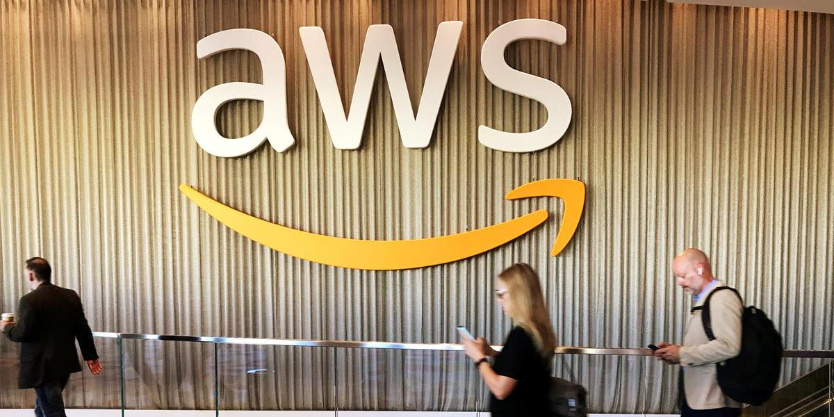 Cloud Computing: Attendees at Amazon's annual cloud computing conference walk past the AWS logo