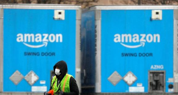 A worker in a face mask walks by trucks parked at an Amazon facility as the global coronavirus outbreak continued in Bethpage on Long Island in New York, U.S., March 17, 2020.