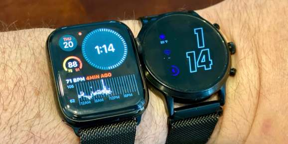 An Apple Watch Series 4 running watchOS 7 next to a Fossil Gen 5 watch running the latest version of Wear OS.