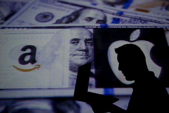 The silhouette of a man with a laptop in front of a pile of cash and the Amazon and Apple logos