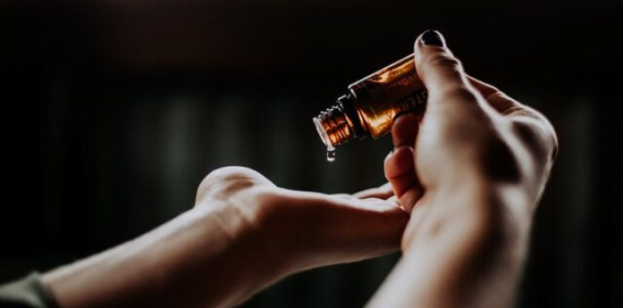 Picture of small oil bottle being dripped into hands