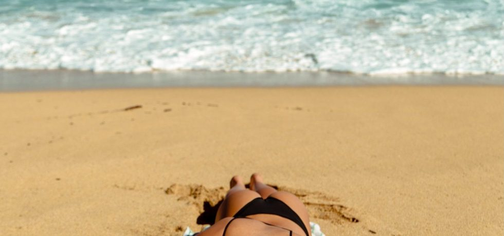 woman laying in the beach with black swimsuit