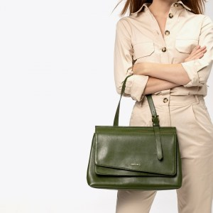 woman dressed on a beige junpsuit with her arms crossed hanging a green croc colour bag from MIOMOJO TECLA BAG brand