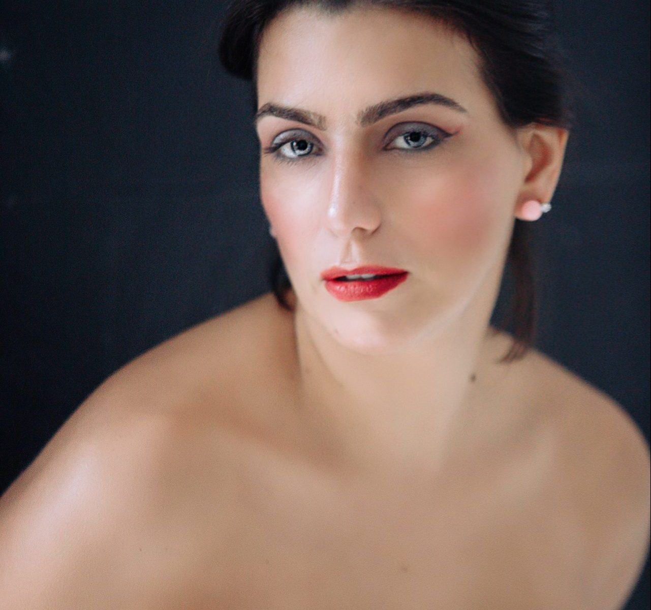 Vera Gallardo a sustainable fashion and beauty blogger wearing a white corpet with no strings with very well done makeup wearing red lipstick and gold earings
