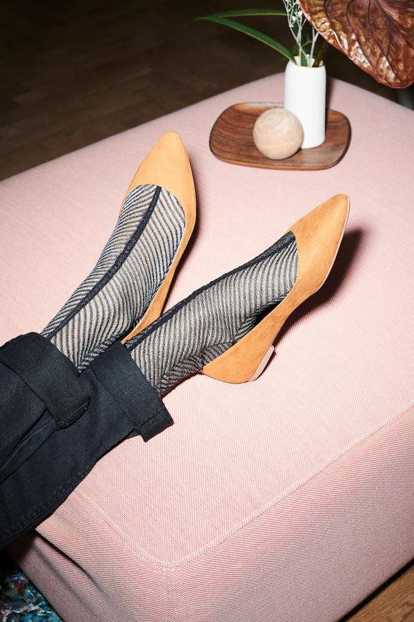 Dear Denier a horsery sustainable brand this image has a pair of shoes point mules yellow color and fishnet stocking inblack with the two legs crosseds