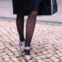 international blogger Vera Gallardo wearing a black litle dress and black fishnet stockings with brillance colouredsandals