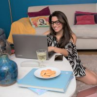 International Fashion and Beauty Blogger Vera Gallardo in her home wearing some loungewear sit down in her carpet working at a table at the pc wearing black squared glasses smiling
