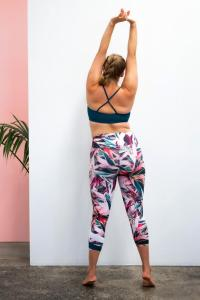 Woman wearing a ELLE EVAN - SetaCrop Leggings she is standing up with her arms up showing her backs