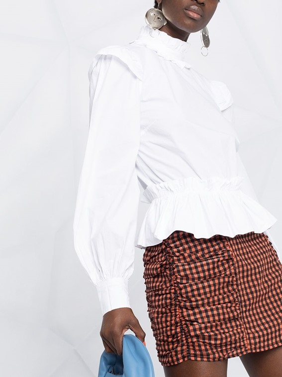 Woman wearing open back ruffle-detail shirt