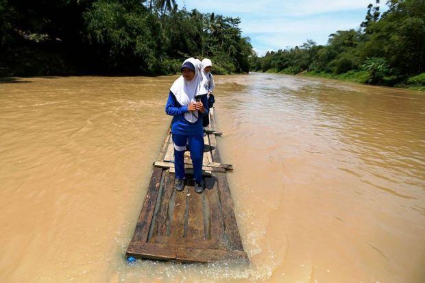 Students crossing Ciherang River on a makeshift bamboo raft