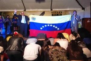 El pastor Doumat (i) y el apóstol Mora (d) sosteniendo la bandera de Venezuela mientras de oraba por nuestro país