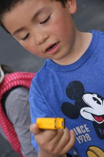 1. Jon Frias, who attends Barron Park Elementary School, plays with a toy truck from the market. The market was started by two Paly parents in 1989. 2. A glass terrarium dangles in the parking lot in front of the Tower Building. 3. A row of scarves hangs on a tent at one vendor's stall. 4. Mini cacti are on display at Shirlui Lam's stall. Lam also sells sun hats and school supplies. 5. Trinkets rest in a glass case, awaiting inspection from potential customers. 6. Handmade jewelry hangs on a stand at a stall in the middle aisle of the market. Many vendors make their own wares.